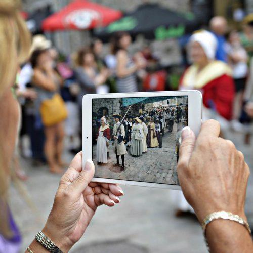 une dame filme un spectacle avec sa tablette