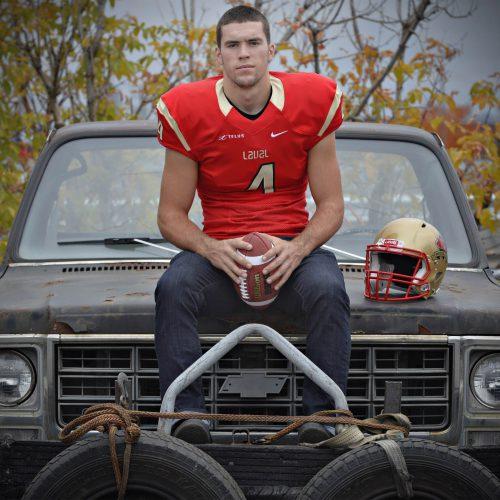 Un joueur de football du rouge et or assis sur le devant d'un vieux camion
