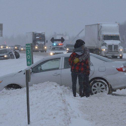 un couple enlacé devant leur auto dans la neige