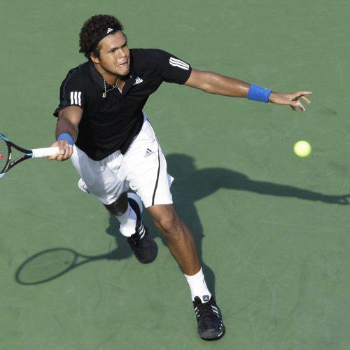 Un homme frappe une balle au tennis