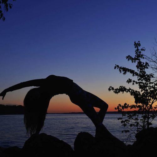 silhouette d'une femme en position de yoga devant un lac