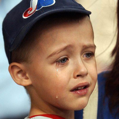Petit garçon avec casquette des expos de Montréal qui pleure