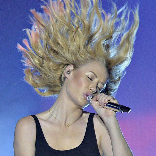 une femme blonde qui chante les cheveux en l'air