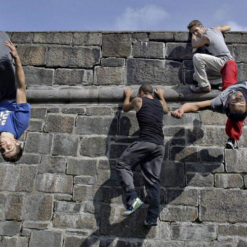 4 jeune hommes sur un mur de parcour