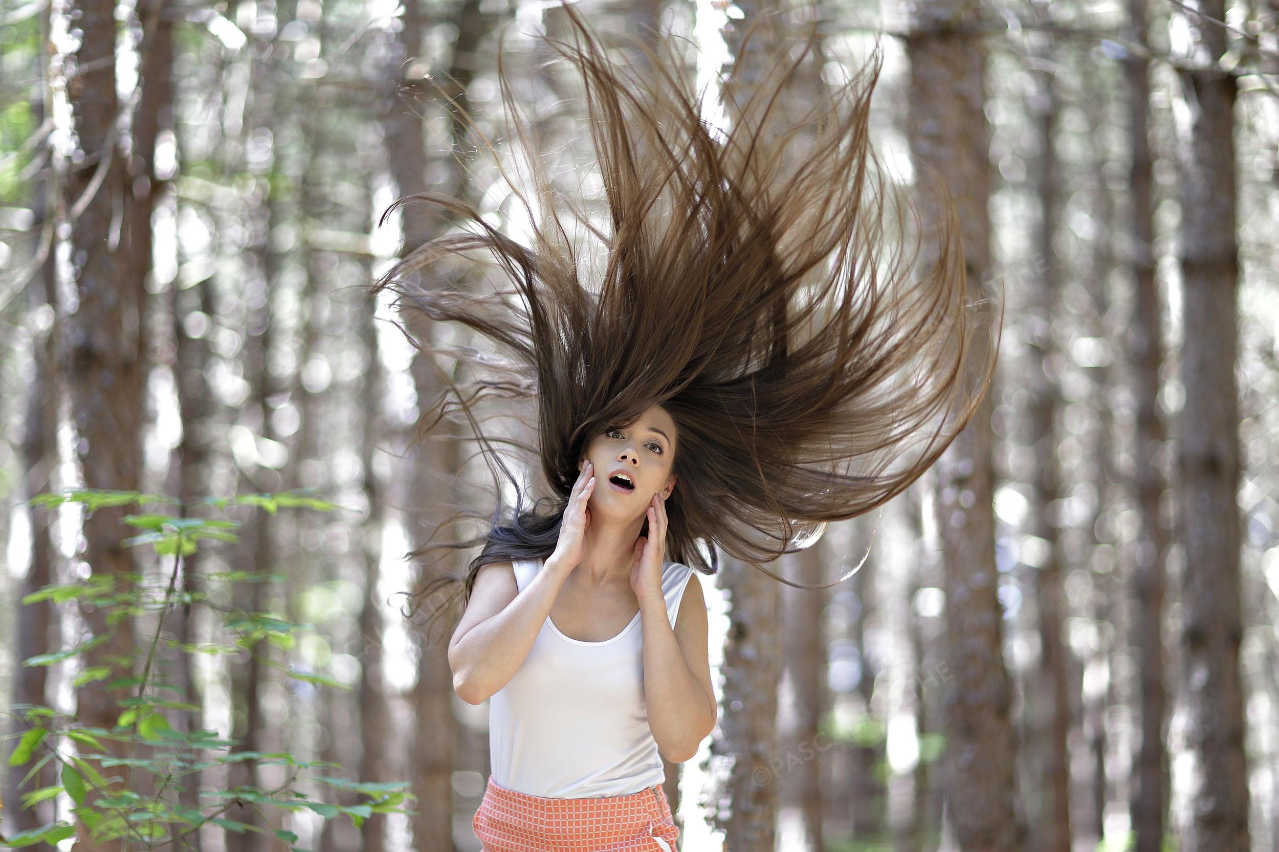 Une brunette dans les bois les cheveux en l'air prise sur le vif