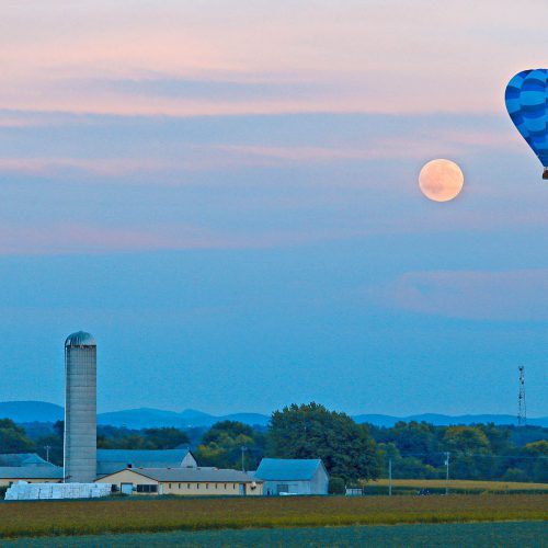 une montgolfière, le soleil et une ferme
