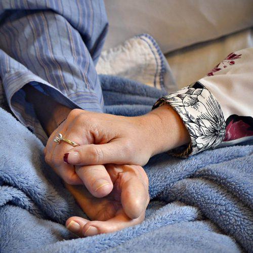 une main de femme tient la main d'une personne agée