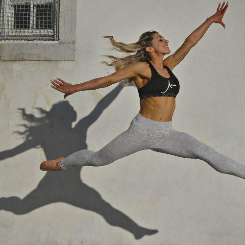 une femme blonde saute dans les airs