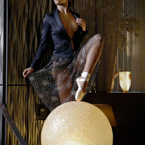 une ballerine le pied sur un gros ballon
