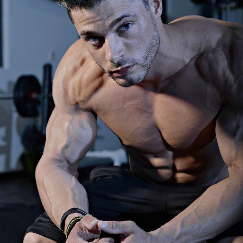 un homme pose sans gilet dans un gym
