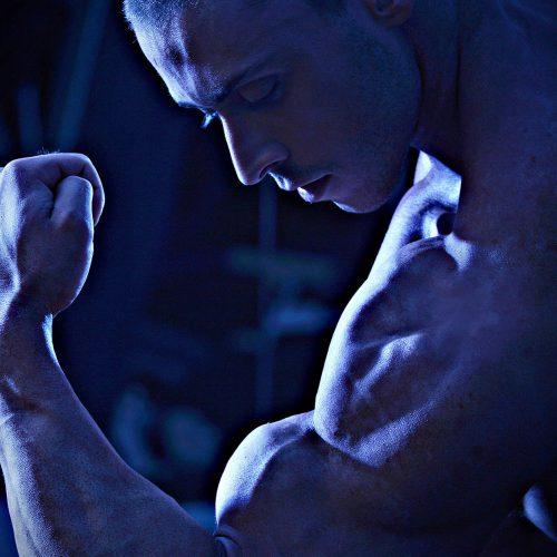un homme pose pour montrer ses biceps