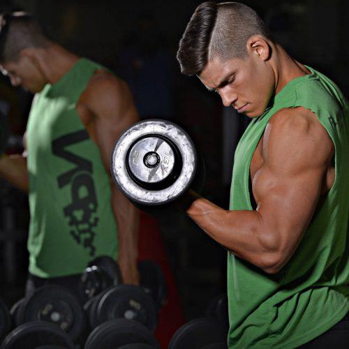 un homme entraine ses biceps devant un miroir