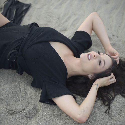jeune femme pose avec une robe noire couchée dans le sable