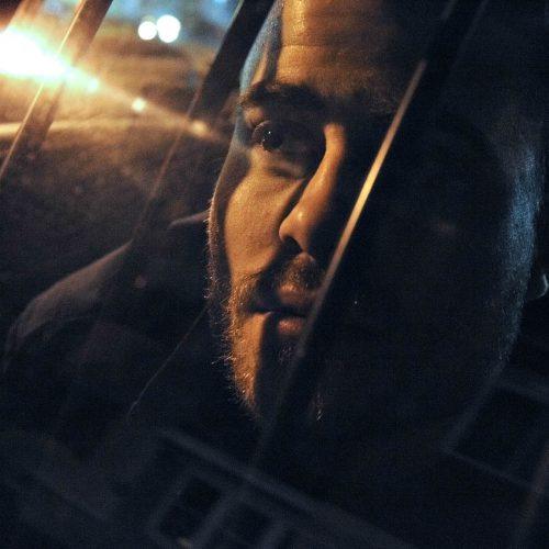 visage d'un homme derrière des barreaux