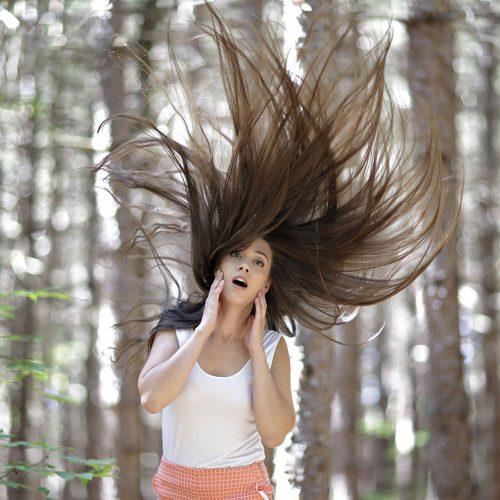 jeune femme dans les bois les cheveux en l'air