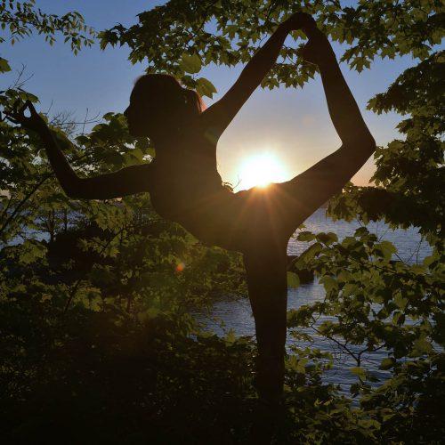 Yoga dans les bois, sur le bord de l'eau au couché du soleil