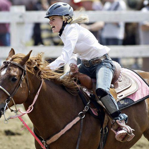 une femme joker course avec son cheval brun