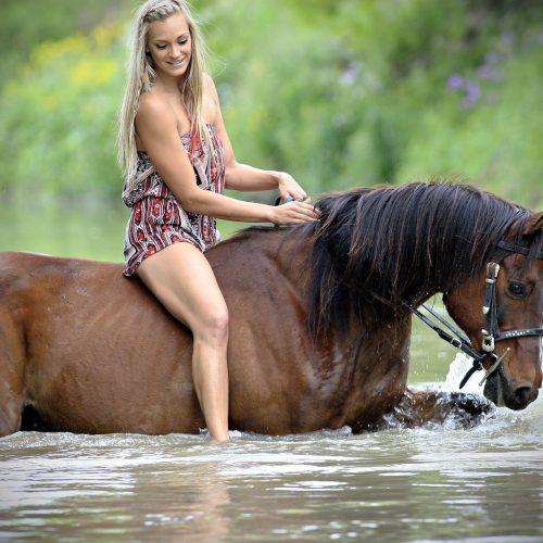une femme blonde traverse l'eau à dos de cheval