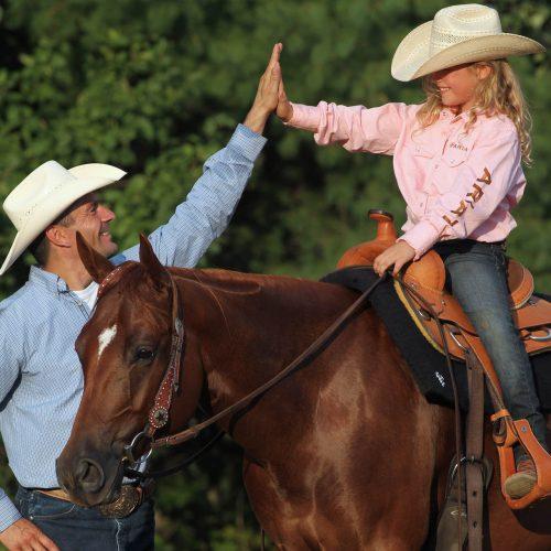 Un homme fait un high five à sa fille sur le dos d'un cheval brun