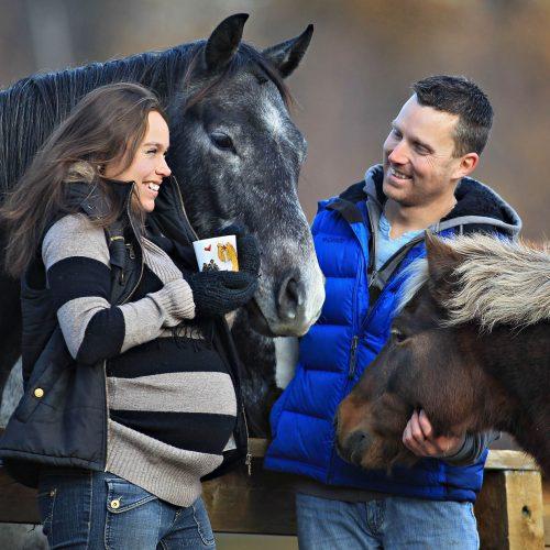 une femme enceinte avec une café à côté d'un cheval et un pony