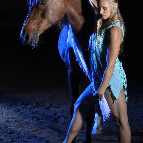 Une femme blonde pose à côté d'un cheval brun de face