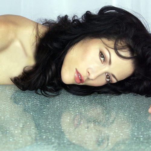 portrait mode d'une belle femme avec son reflet dans une table de crystal