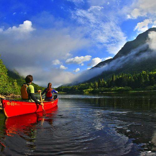 2 personnes en canot sur la rivière jacques-cartier pendant une belle journée d'été avec un beau ciel bleu