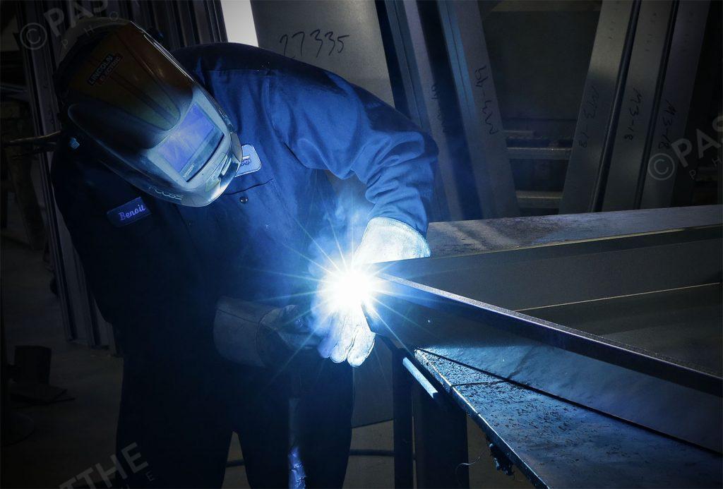 photo d'un soudeur qui soude des plaques d'aluminium ce qui produit une belle lumière bleu