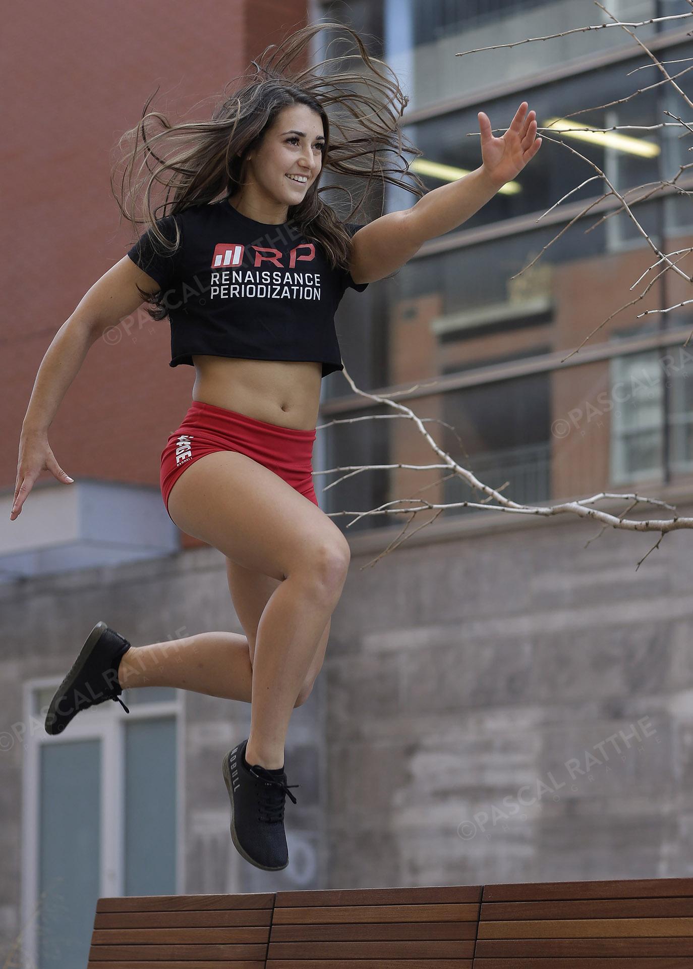une femme sportive qui s'active dehors au printemps en sautant dans les air