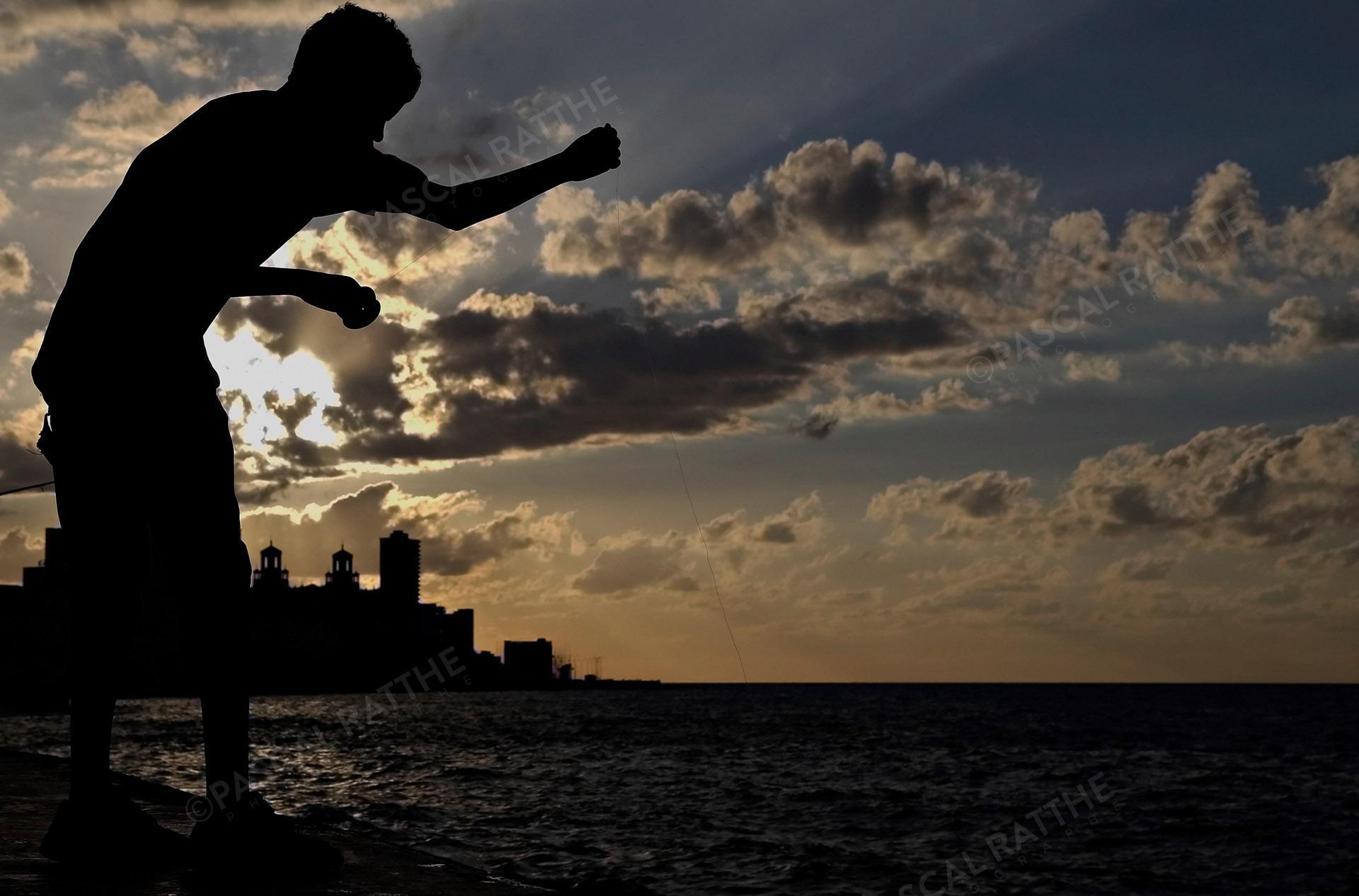 couché de soleil à la havane, Le Malecon, un jeune pêcheur