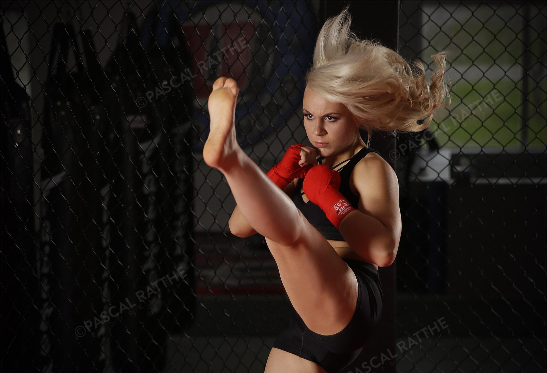 Émilie Gendron une jeune femme athlète de mma donne un coup de pied dans les air avec un regard furieux