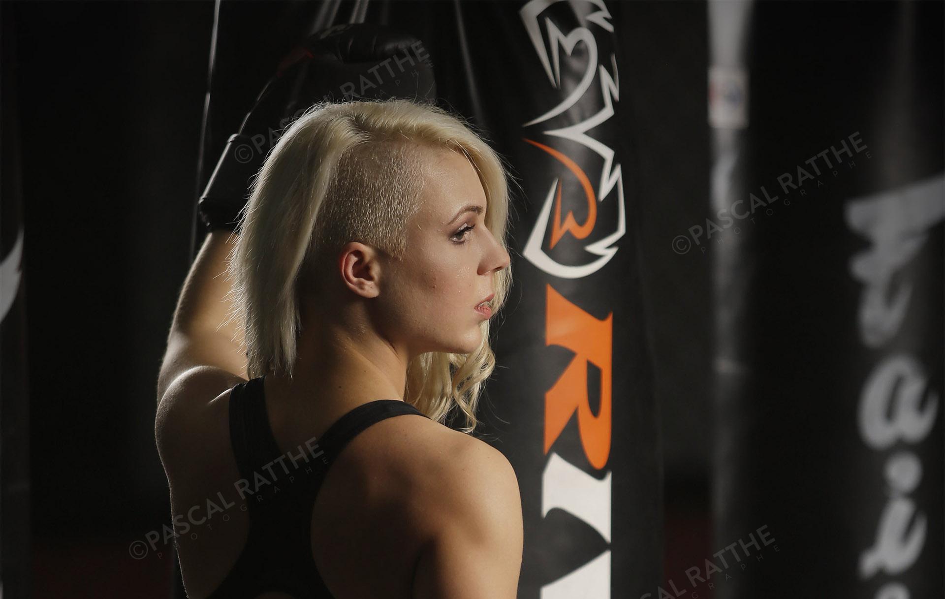 Émilie Gendron une jeune femme athlète de boxe frappe des gros sacs d'entrainement