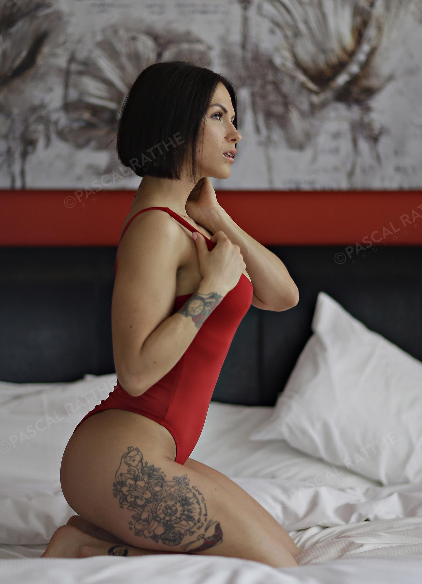 Annie Lizotte scéance photo d'une femme en maillot rouge sexy et en forme sur un lit