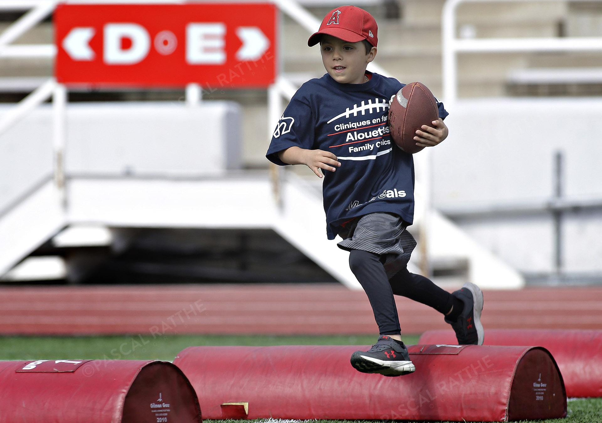 Cliniques Football des Alouettes de Montréal un jeune enfant saute avec un ballon par dessus un sac rouge