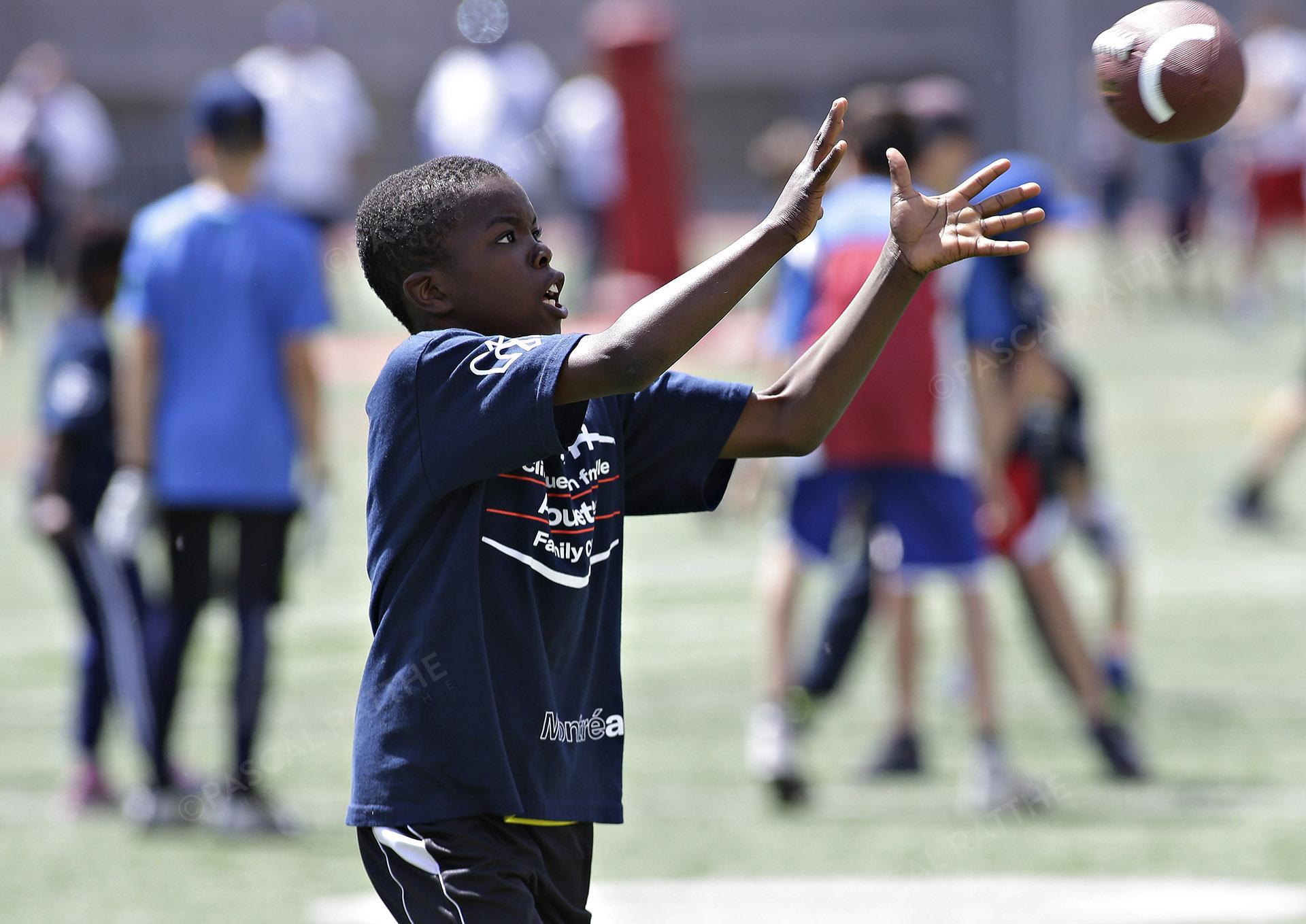 Cliniques Football des Alouetes de Montréal, un jeune enfant attrape le ballon