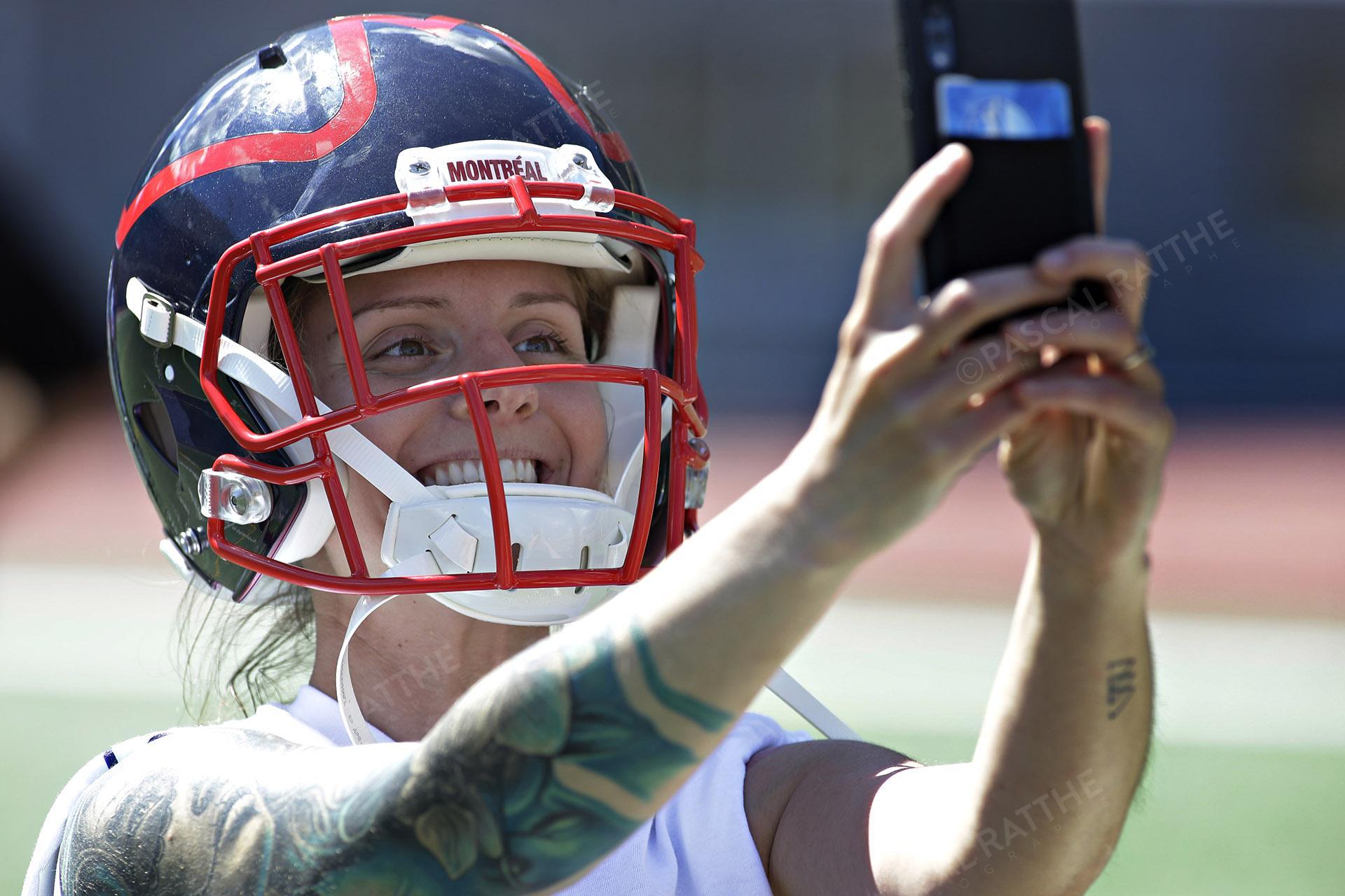 une fan des Alouettes de Montréal se prend en Selfie avec un Casque de Football à la clinique de football