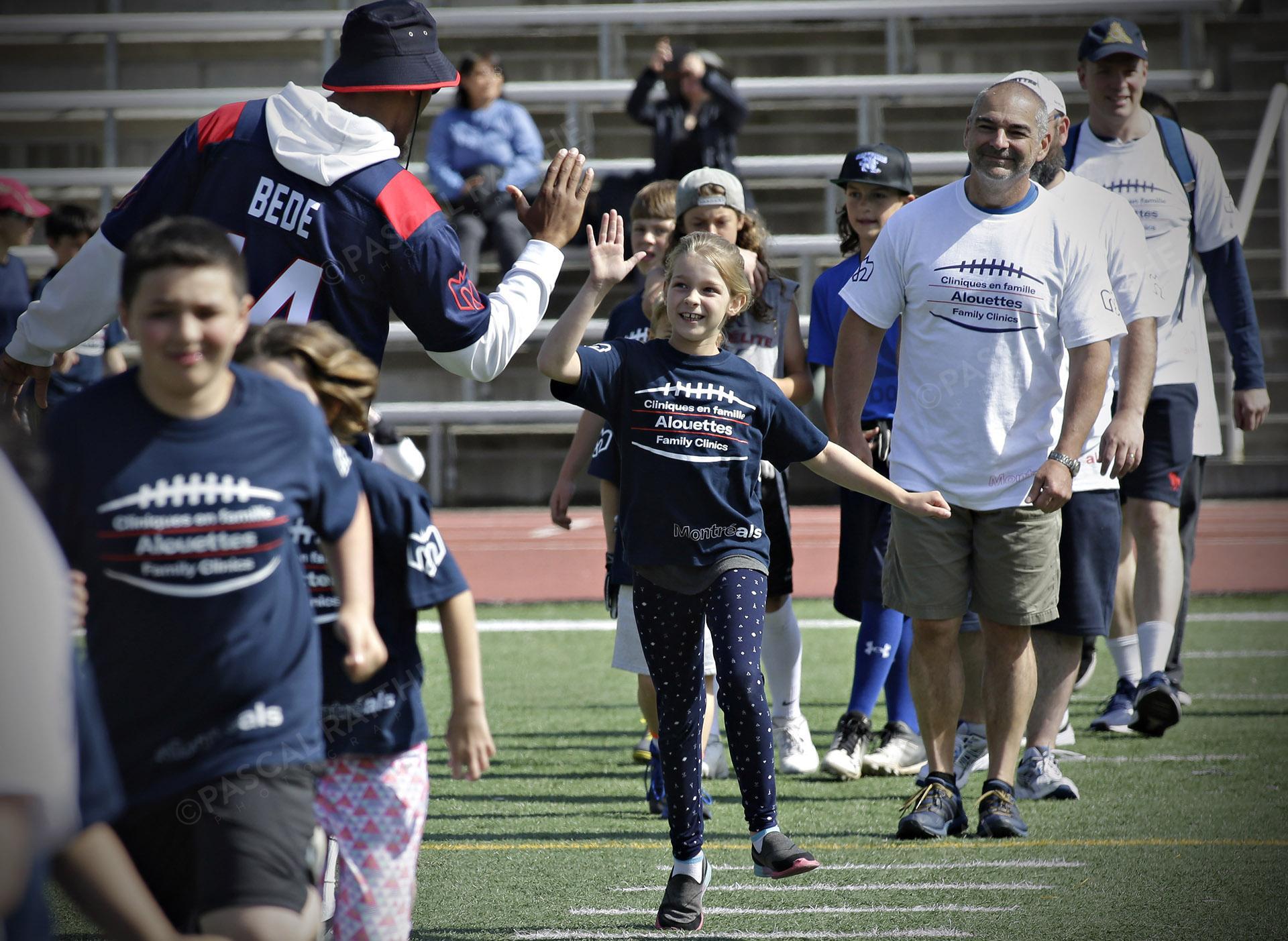 Cliniques Football des Alouettes de Montréal plusieurs enfants avec un joueur des Alouettes
