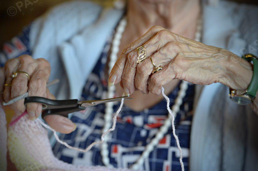 les mains d'une personne âgé faisant du tricot