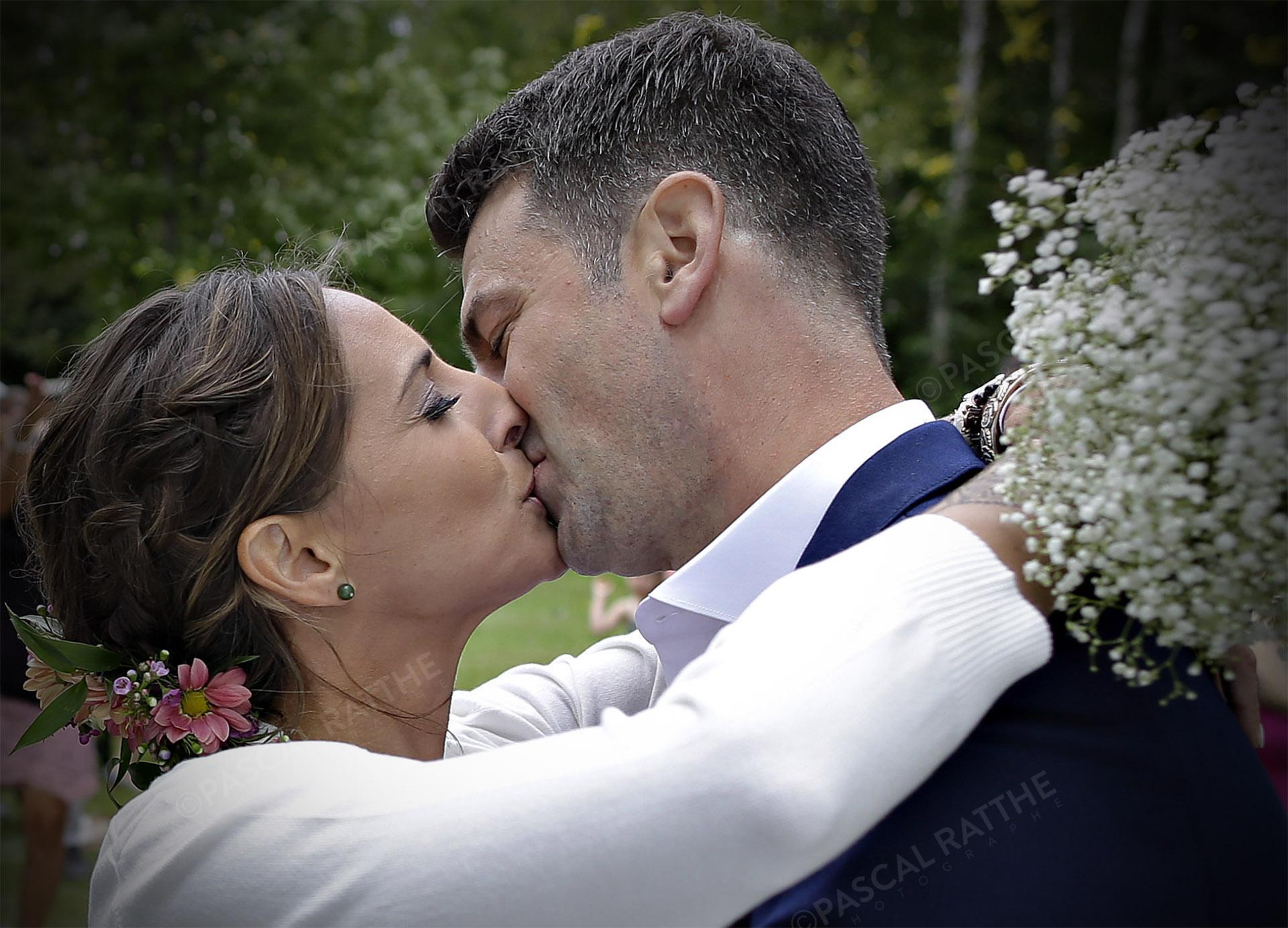 deux nouveaux mariés s'embrassent avec passion durant la cérémonie de mariage