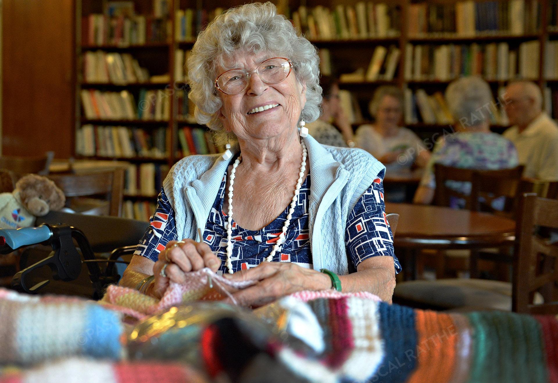 les mainpersonne âgé avec un grand sourirefaisant du tricot