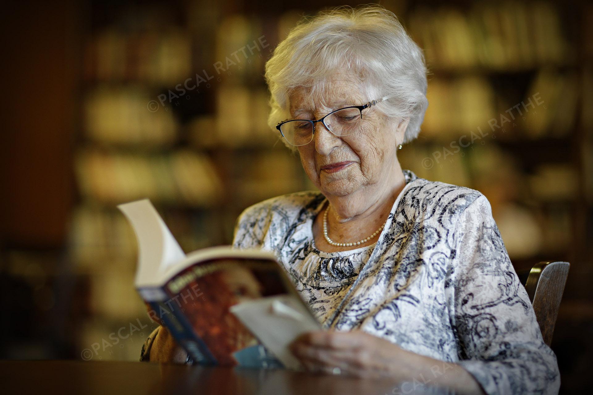 une personne du 3e âge lisant un livre