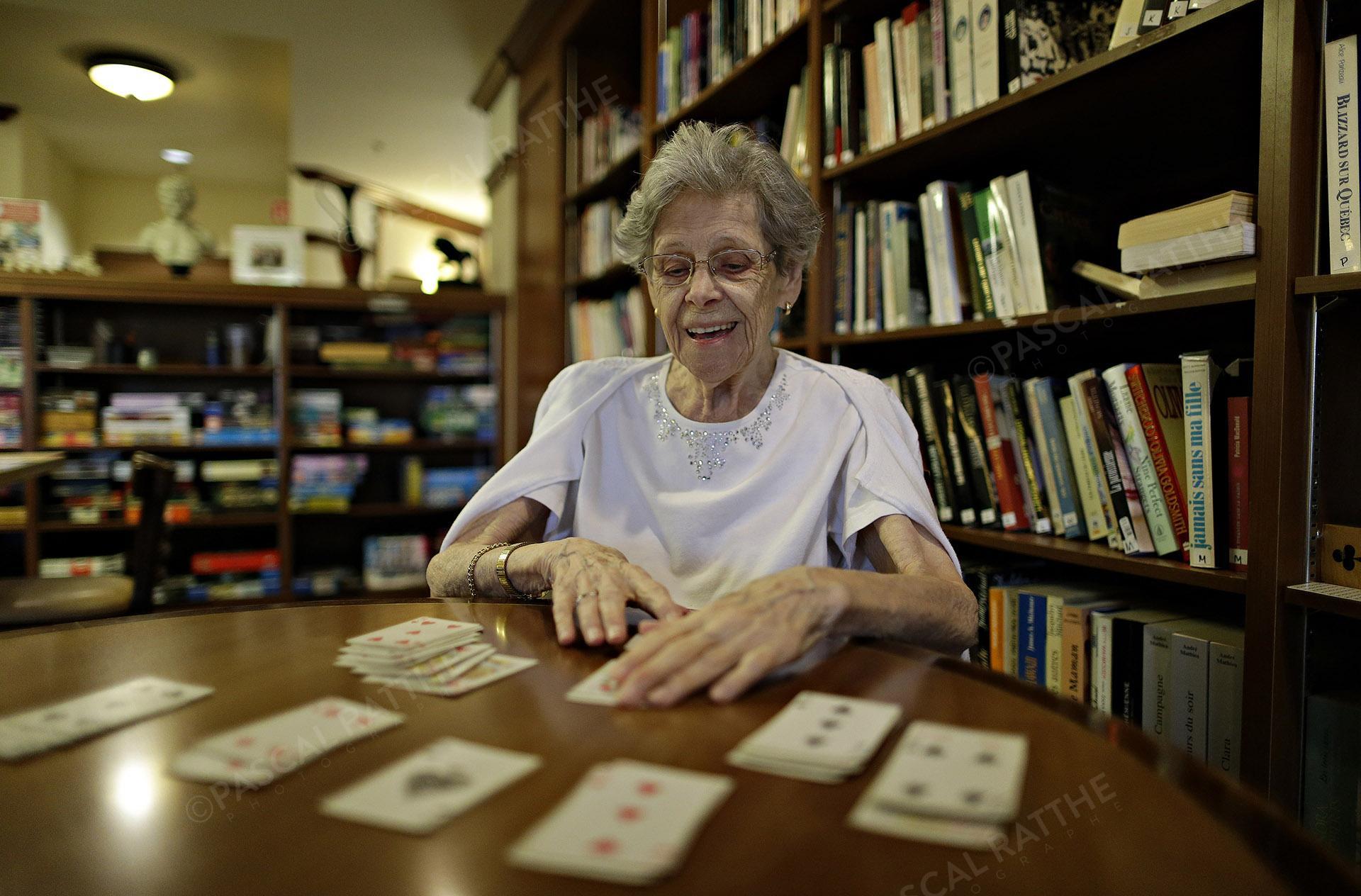une dame du 3e âge avec un sourire éclantant jouant aux cartes