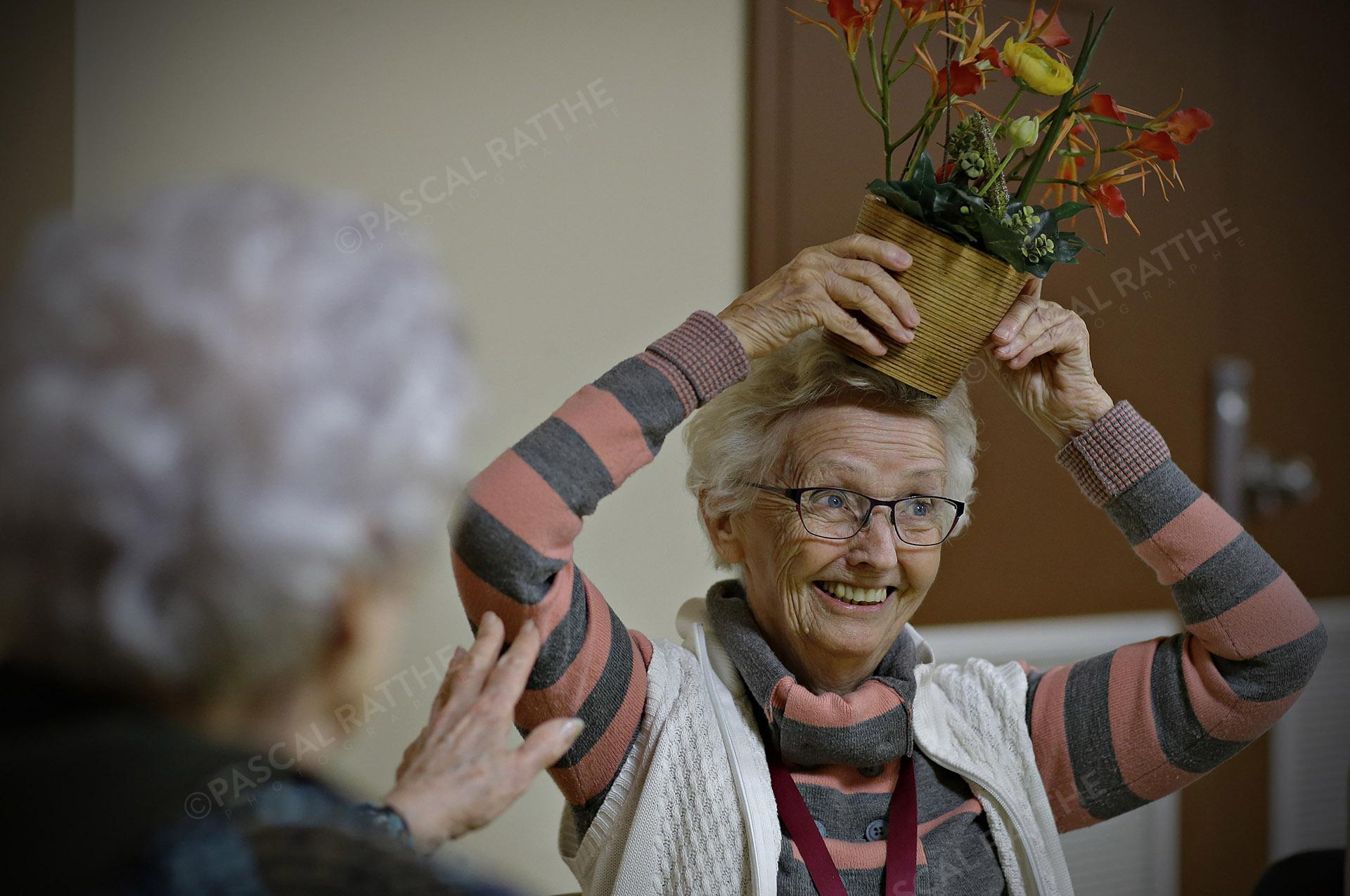 une dame du 3e âge avec un sourire éclantant et un pot de fleur sur la tête